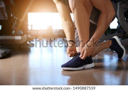 Sporty young man tying shoelaces in gym