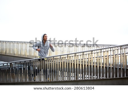 Sporty young man working out at early morning while run up the bridge with overcast sky on background, male jogger exercising while listening to music with headphones, runner working out outdoors