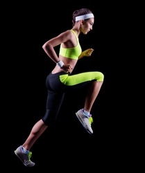 Sporty young running girl on black