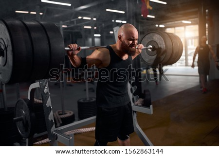 Sporty young weightlifter training in modern gym using barbell row, standing near metal bar in dark lighted room, preparing for competition of powerlifting, portrait, side indoor shot,