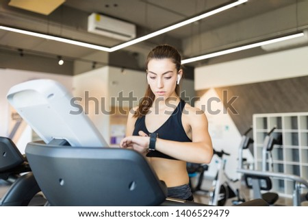 Sporty young woman checking time on exercise machine in health club