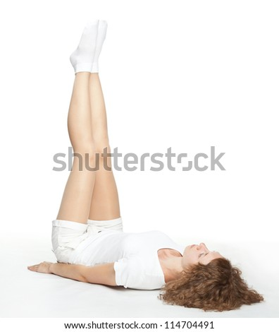 Sporty young woman doing gymnastics lying on the floor