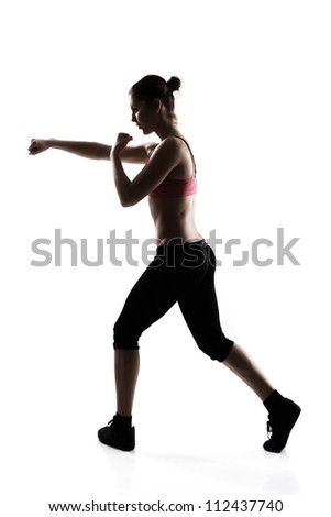sporty young woman doing martial arts exercise, silhouette studio shot over white background