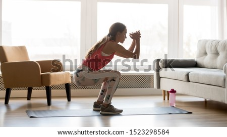Sporty young woman doing squat morning exercise alone in living room, serious fit girl wearing sportswear crouching training muscles workout at home for healthy body lifestyle concept, side view