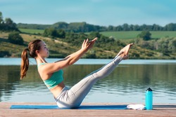 Sporty young woman doing stretching while sitting in Paripurna Navasana exercise, balance posture. Athletic girl practicing yoga against the backdrop of beautiful nature.Healthy concept.Teaser exercis