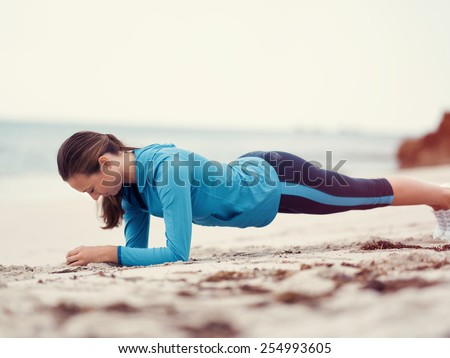 Sporty young woman exercising  on the sea coast