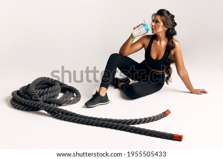 Sporty young woman in black suit is resting while sitting on the floor and drinks water from a bottle, after crossfit workout with ropes on an isolated white background. hard workout Сток-фото ©