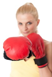 Sporty young woman in red fighting gloves on a white background. Selective focus on gloves.