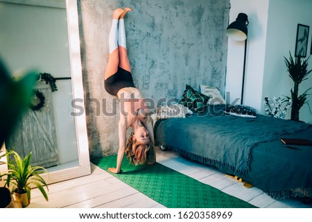 Sporty young woman in sportswear exercising yoga asana in handstand leaning legs on wall in modern bedroom training at home