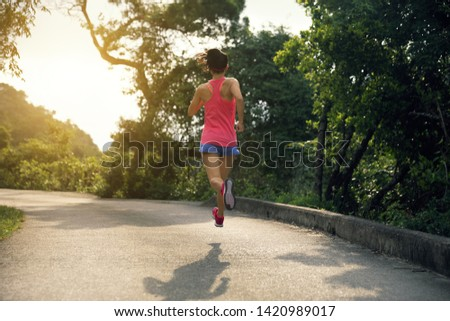 Sporty young woman in sportswear trail running on forest mountain path. Fitness girl jogging in Hong Kong