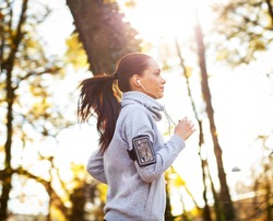 Sporty young woman running in the park and listening to music. Sport lifestyle. Motion blur.