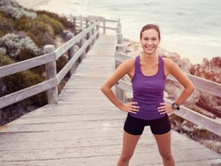 Sporty young woman standing on the sea coast