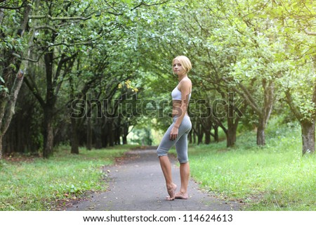 Sporty young woman stay barefoot in park after sport excises.  Yoga woman. Young fit bootless woman in the morning park. Foot free.