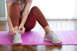 Sporty young woman tying the shoe laces on exercise mat in living room