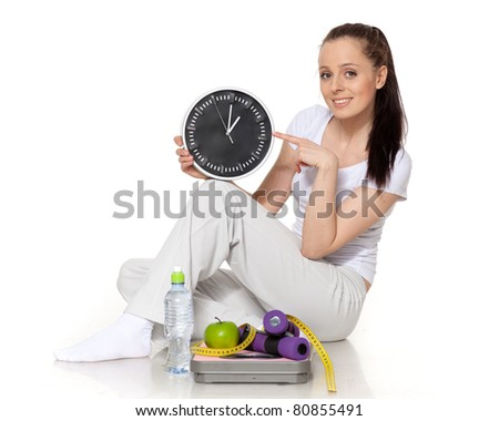 Sporty young woman with clock, scales, dumbbells and apple on a white background.  Time for slimming.