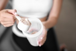 Sporty young woman with protein at home, closeup