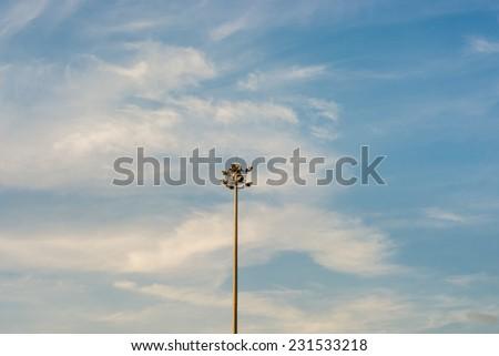 Spot light pole with blue sky.