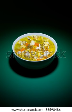 Spot of light on bowl of hot soup on green table