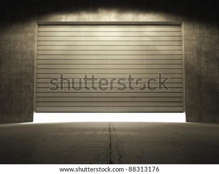 Spotlight illuminate building of grungy concrete with roller shutter door