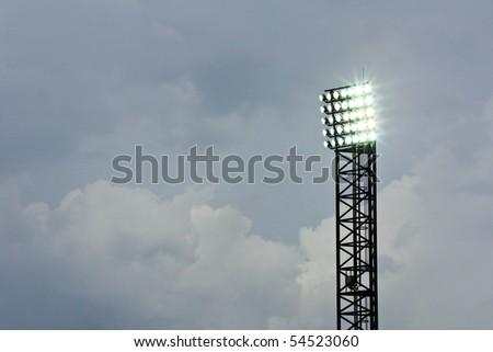 Spotlight of football stadium is lighting up beautiful background cloud - stock photo