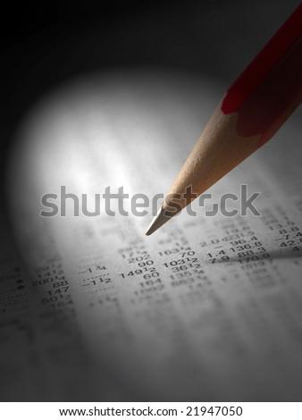Spotlight shining on pencil over financial newspaper
