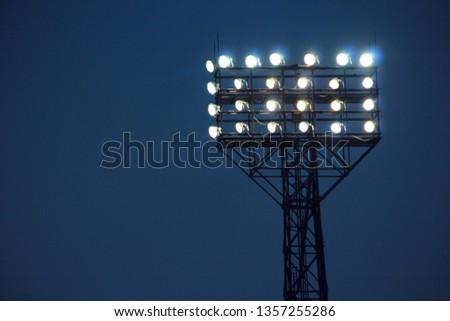Spotlights illuminate football field during match. Lighting equipment for stadiums. Powerful lighting in stadium