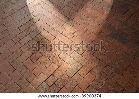 Spotlights shining on red brick pavement walkway patio floor