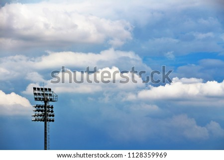 Spotlights, spotlights in the stadium, and blue skies and clouds. #1128359969