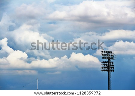 Spotlights, spotlights in the stadium, and blue skies and clouds. #1128359972