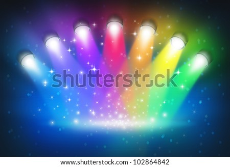 Spotlights with rainbow colors as a magical abstract background of a concert lighting on a dark glowing theater stage with shiny sparkles with a blank center as a symbol of entertainment.
