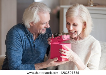 Spouses celebrating special occasion, grey haired husband giving to loving pretty happy wife pink gift box with long awaited present, she feels excited and satisfied. Making joy to loved ones concept