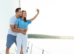Spouses On Cruise Yacht Making Selfie On Smartphone Standing On Sailboat Deck Outside. Sea Adventure Concept
