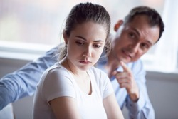 Spouses quarreling at home, frustrated wife listen claims from angry husband, focus of female. Head shot married couple have bad difficult relations. Break up unexpected pregnancy and divorce concept