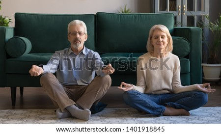 Spouses sitting in lotus pose on warm floor in living room, sixty years serene wife husband meditating do breath exercises feels calmness and serenity, yoga time, healthy lifestyle of retirees concept #1401918845