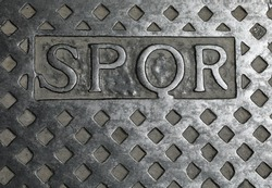SPQR text on the metal manhole is the abbreviation of the city of rome in italy and means The Roman Senate and People in italian language