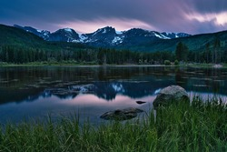 Sprague lake in colorado. Long exposure sunset in rocky mountain national park. Colorado rockies mountain visible in the distance. Colorful sunset with fiery clouds