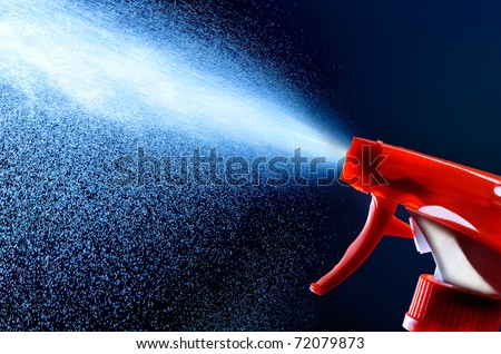 spray bottle - lighted while spraying on dark background
