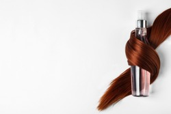 Spray bottle wrapped in lock of hair on white background, top view. Natural cosmetic products