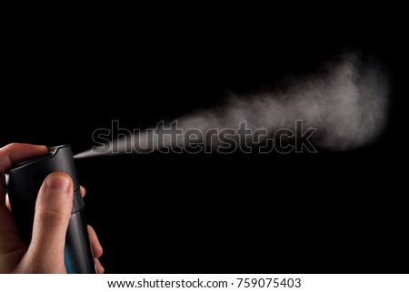 Spray can in hand and aerosol in white color isolated on black background, close up