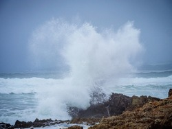 Spray from a wave crashing onto the rocky shoreline at Hermanus, Whale Coast, Overberg, Western Cape. South Africa.