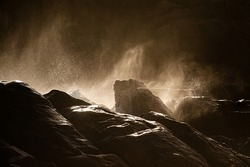 Spray from breaking waves against dark rockface