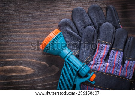 Spray hose nozzle and black rubber safety gloves on vintage wood board gardening concept.
