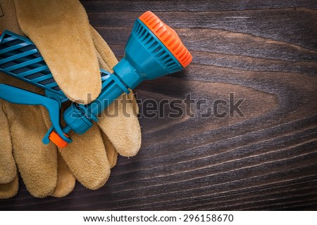 Spray hose nozzle and leather working safety gloves on brown vintage wooden board gardening concept.