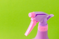 spray nozzle on a bottle/purple spray nozzle on a bottle on a green background. Copy space.