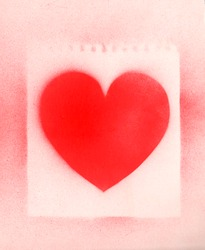 Spray paint heart sign, shape heart graffiti on white paper background with perforation traces