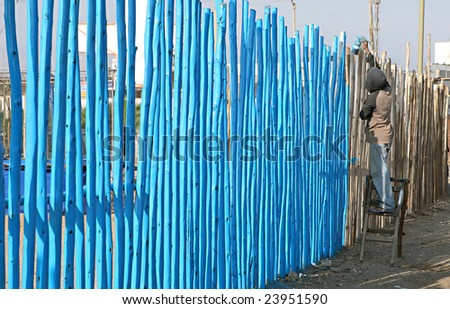 Spray painting a wooden fence in Peru