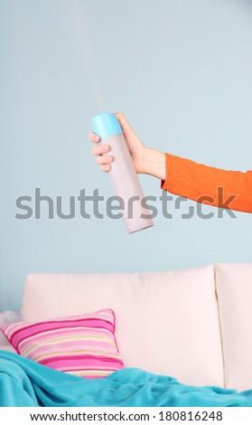 Sprayed air freshener in hand on home interior background