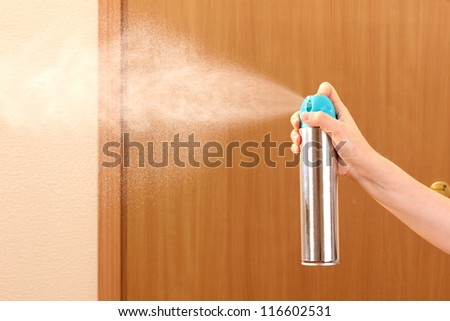 Sprayed air freshener in hand on room background