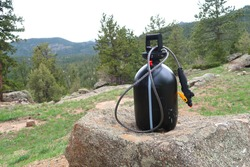 Sprayer spray painted black to serve as a solar heated camp shower. Sprayer sits on a boulder at a campsite in the mountains.