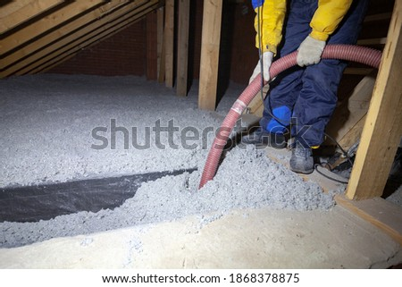 Spraying cellulose insulation in the attic of a house. Insulation of the attic or floor in the house Stock photo ©